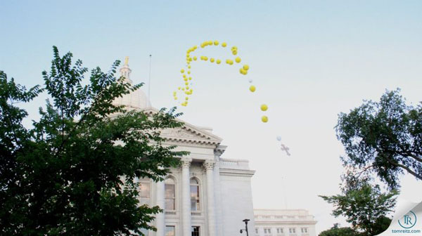 The balloon rosary floats past the Capitol Dome
